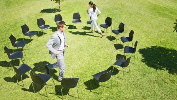 """Dos personas dando vueltas en el """"juego de las sillas musicales"""""""