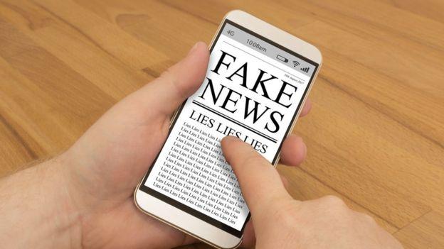Celular com ilustração de fake news