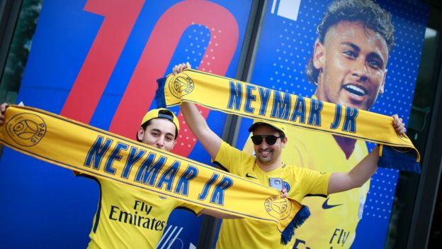 Aficionados frente a un poster publicitario de Neymar