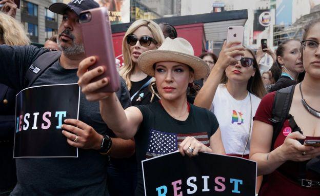 Alyssa Milano rodeada de gente con sus móviles.
