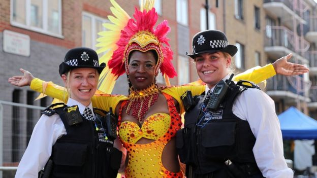 Police officers stand with a carnival performer