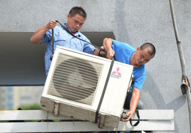 Hombres bajando un aire acondicionado.