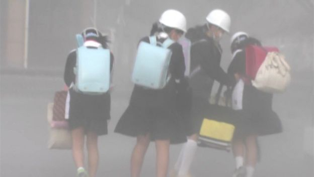 schoolgirls wearing helmets and face masks