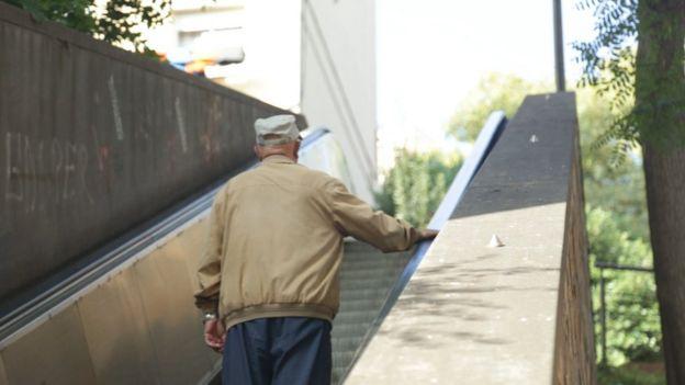 Un hombre anciano sube una escalera mecánica.