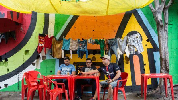 amigos bebendo em bar de favela