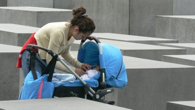 Mujer con bebé en el memorial
