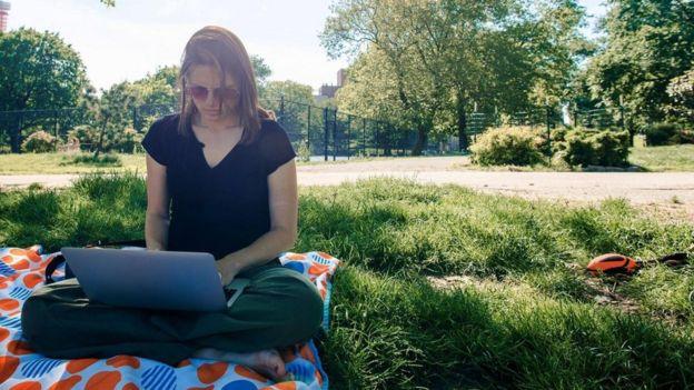 Una joven usando su laptop en un parque
