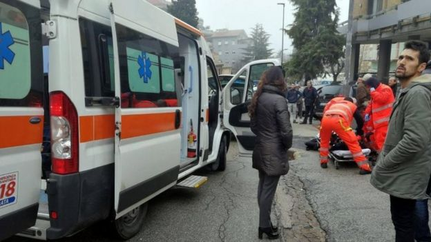 Paramedics treat an injured person that was shot from a passing vehicle in Macerata, Italy, 3 February 2018