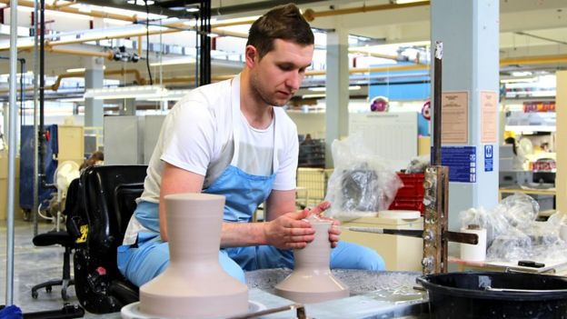 Chris Mottram, shapes the clay on the potter's wheel, a skill he learned from another potter.