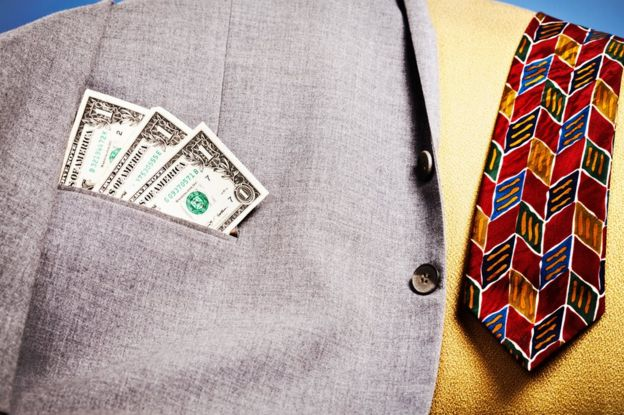 Dollar bills stick out of the pocket of a jacket left on a sofa, next to a tie.