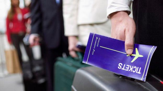 hombre sosteniendo billete de avión