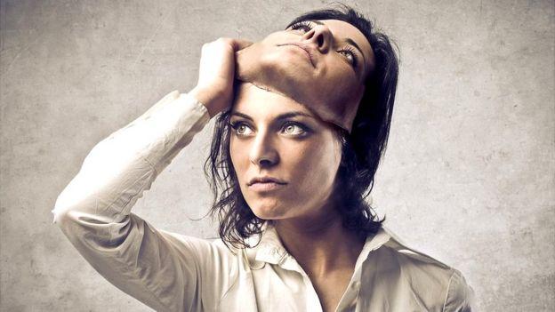 Una mujer se quita una careta.