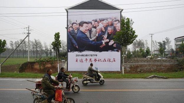 Cartaz do presidente Xi Jinping visitando pessoas que vivem na pobreza
