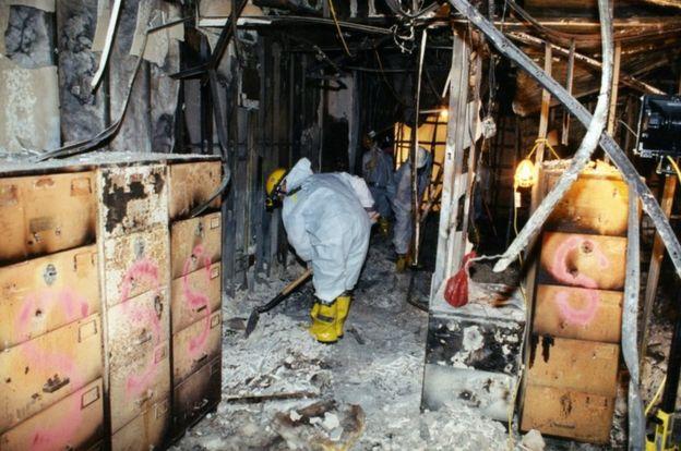 محققون يجرفون الرماد بعد اطفاء الحريق داخل المبنى