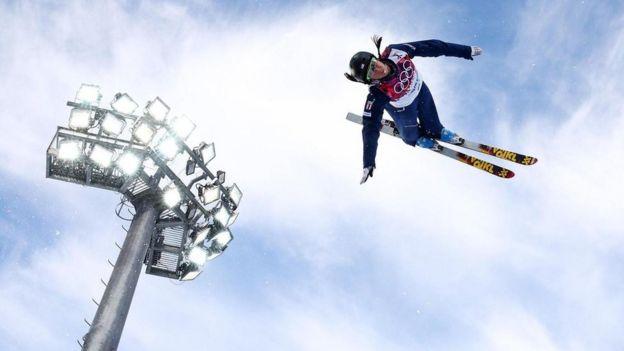 Un hombre dando con un salto con esquís.