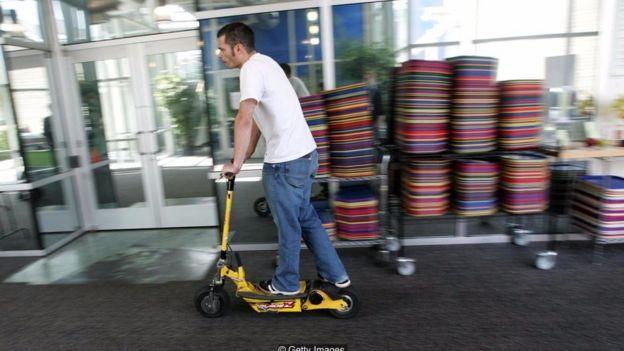 Nhân viên Google đang đi chiếc xe Go-Ped scooter qua phòng ăn.