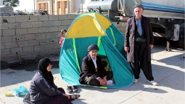 Mulher e dois homens em barraca com criança ao fundo