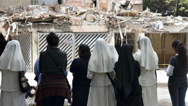 Varias mujeres, entre ellas religiosas, miran un edificio derrumbado en la Ciudad de México.