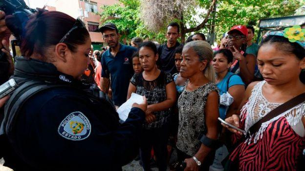 Una policía dando información a los familiares de los presos.