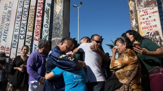 Families embrace after opening the door on the US-Mexico border