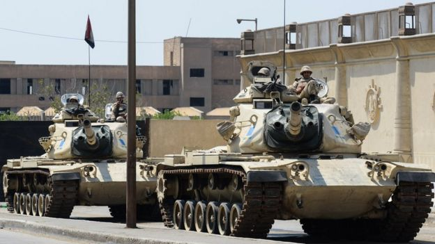 File photo showing Egyptian military tanks outside the police institute, near Cairo's Torah prison (10 April 2014)