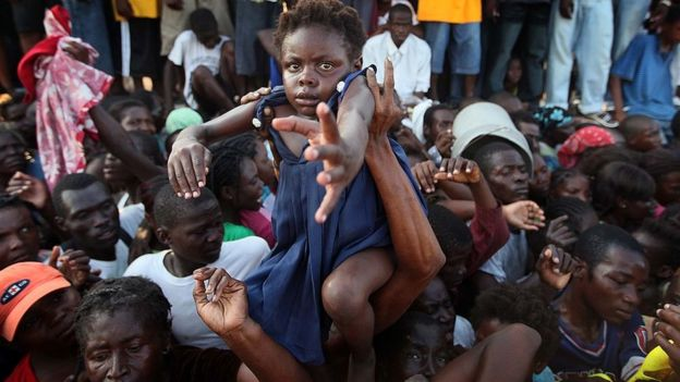 Una niña es levantada en brazos en medio de una multitud de gente en Haití.
