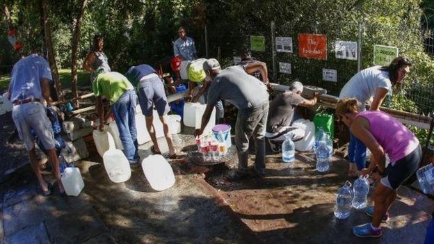 Un grupo de personas recoge agua de un manantial en Ciudad del Cabo.
