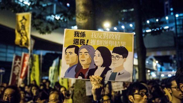 示威者拿著牌子,抗議香港當局取消四名非建制派議員的資格