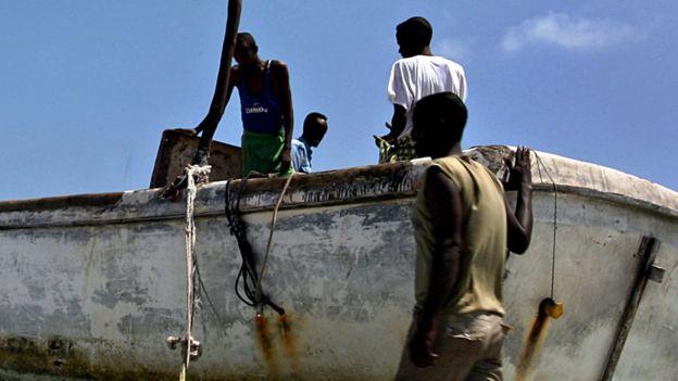 Un grupo de hombres junto a un barco.