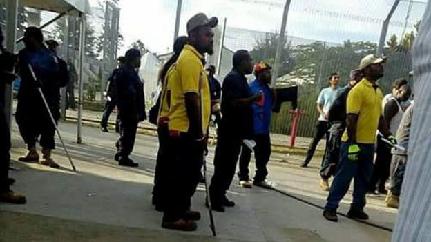 PNG police and immigration officials holding poles in the Manus detention centre