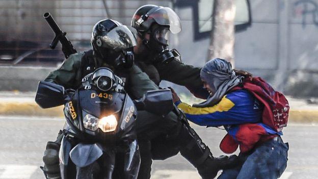Dos agentes agarran a un manifestante