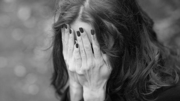 женщина, закрывшая лицо руками