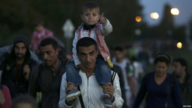 A migrant carries a child as he walks into Austria