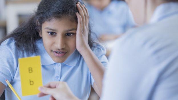 Una niña intenta leer con dificultad una tarjeta con las letras