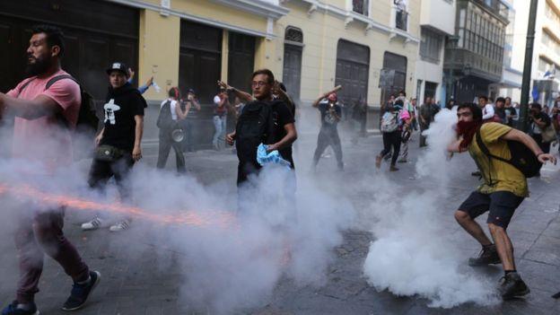 Manifestantes protestando contra el indulto en medio de gases lacrimógenos.