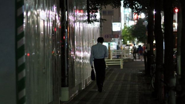 Tokyo sokaklarında yürüyen bir iş adamı.