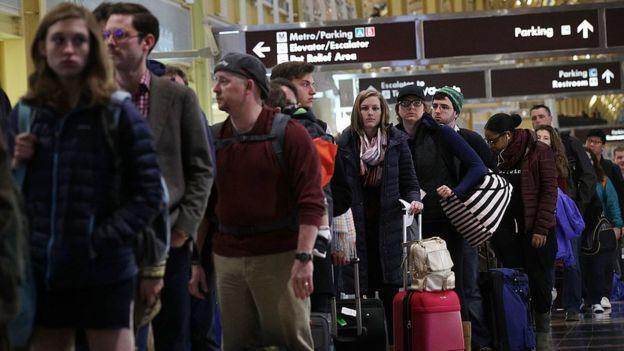 Pasajeros hacen fila en un aeropuerto.