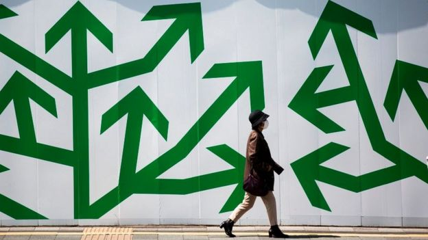 A pedestrian walks past decorated panelling used to shroud a construction site along a street in Tokyo