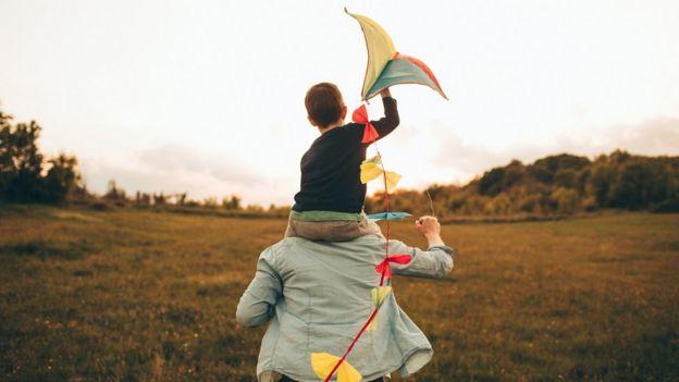 بچهای که روی دوش پدرش بادبادک هوا میکند