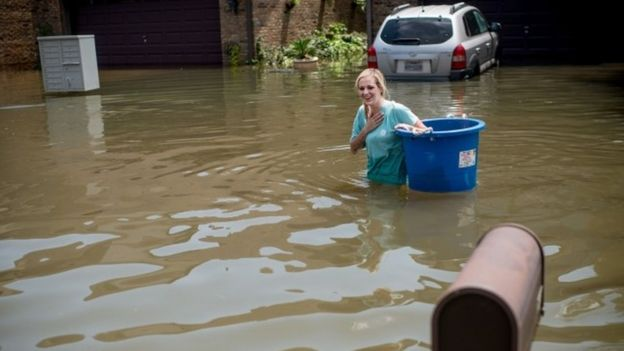 Jenna Fountain carries a bucket down flooded Regency Drive in Port Arthur, Texas, September 1, 2017
