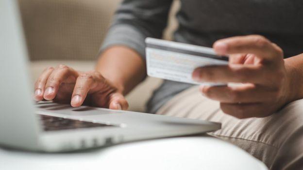 hombre pagando con tarjeta en una computadora