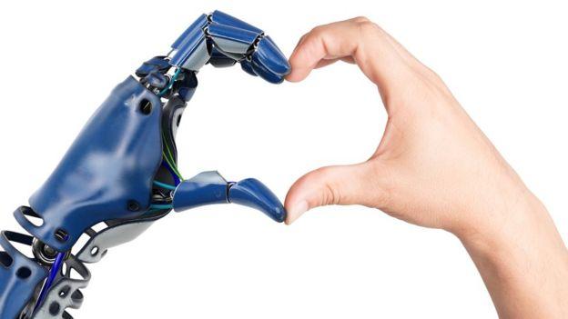 Mano robótica y mano humano haciendo la forma de corazón