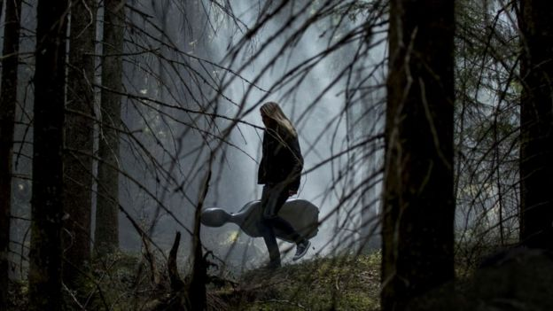 Girl calmly walking through a Finnish forest in the dark with her instrument