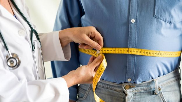 Una médica midiendo el abdomen de un hombre.