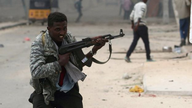 Somali government soldiers run to take their positions during gunfire after an attack at a hotel in Mogadishu on 25 June