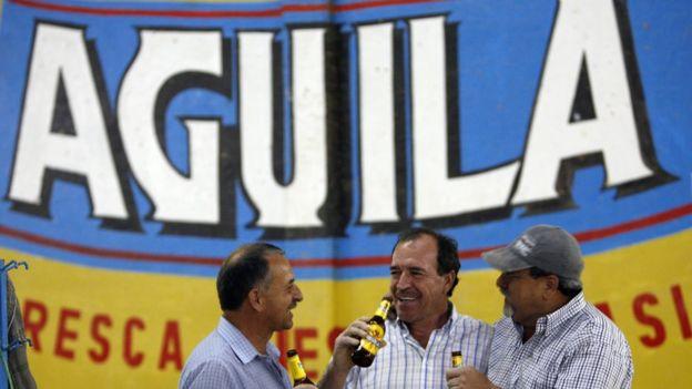 Três homens tomando cerveja Águila
