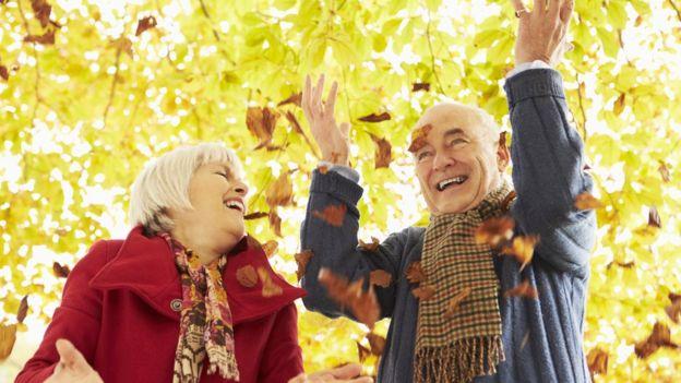 Sonbaharda dökülen yapraklarla oynayan yaşlı bir adam ve bir kadın.