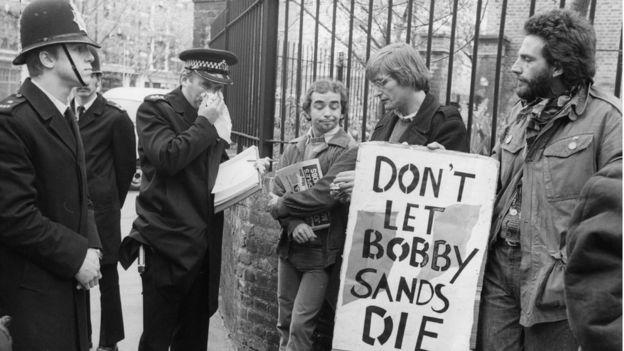 Manifestante segura placa em que se lê 'Don't let Bobby Sands die'
