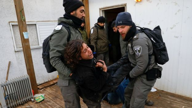 Policías israelíes evacúa el asentamineto de Amona.