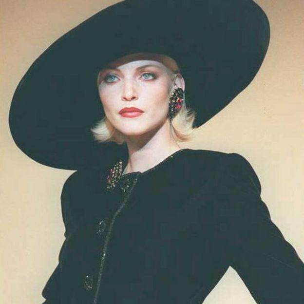 A model in large black hat, tilted to side and velvet black dress in July 1995